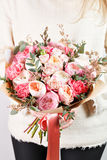 Collection of different varieties of garden roses, carnations and eucalyptus. Girl`s hands holding gentle colors flowers Stock Images