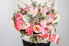 Collection of different varieties of garden roses, carnations and eucalyptus. Girl`s hands holding gentle colors flowers Royalty Free Stock Image
