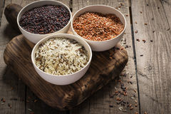 Collection of different varieties of rice on wooden rustic background Stock Photography