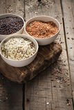 Collection of different varieties of rice on wooden rustic background Stock Photos