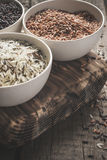 Collection of different varieties of rice on wooden rustic background Royalty Free Stock Images