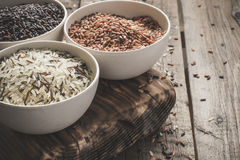 Collection of different varieties of rice on wooden rustic background Royalty Free Stock Photos
