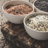 Collection of different varieties of rice on wooden rustic background Royalty Free Stock Photo