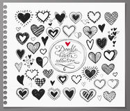Collection of doodle sketch hearts hand drawn with ink and isolated on realistic lined paper. Royalty Free Stock Images