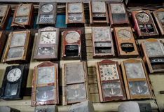 Collection of dusty wall pendulum clocks in junk shop, vintage background Royalty Free Stock Image