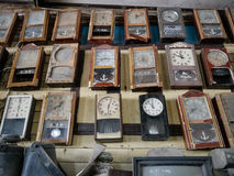 Collection of dusty wall pendulum clocks in junk shop, vintage background Royalty Free Stock Photography