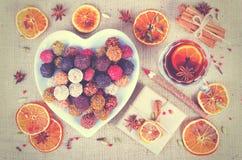 Collection faite main de bonbons au chocolat, oranges sèches, épices, vin chaud, crayon en bois sur le fond en bois Photographie stock
