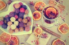 Collection faite main de bonbons au chocolat, oranges sèches, épices, vin chaud, crayon en bois sur le fond en bois Images libres de droits