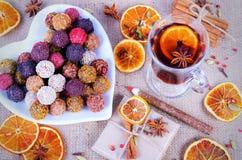 Collection faite main de bonbons au chocolat, oranges sèches, épices, vin chaud, crayon en bois sur le fond en bois Photo stock