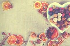 Collection faite main de bonbons au chocolat, oranges sèches, épices, vin chaud, crayon en bois sur le fond en bois Image stock