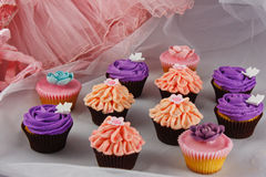 Collection of festive cupcakes. A collection of orange, purple and pink iced cupcakes Royalty Free Stock Photo