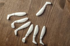 Collection of fish, silicone baits of white color on a brown table, wooden background Royalty Free Stock Image