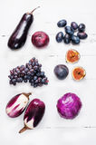 Collection of fresh purple fruit and vegetables on wooden background.  Royalty Free Stock Images