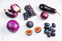 Collection of fresh purple fruit and vegetables on wooden background.  Royalty Free Stock Image