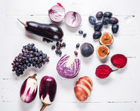 Collection of fresh purple fruit and vegetables on wooden background.  Stock Images