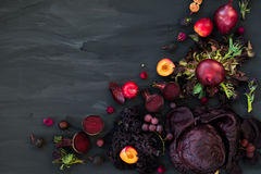 Collection of Fresh Purple Fruits and Vegetables. Such as Plums, Beetroots, Onions, Aubergine, Lettuce, Cabbage, Beans, Figs, Grapes on the Dark Background with Royalty Free Stock Photos