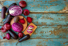 Collection of fresh purple vegetables on the blue wooden backgro. Und with top view  ready for your design Stock Photos