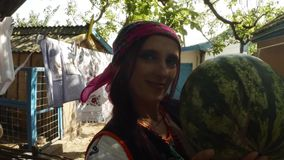 A young woman in a Ukrainian folk costume holds a watermelon in the hands of a drying laundry in a rural yard. Collection, a girl in a traditional Ukrainian folk stock footage