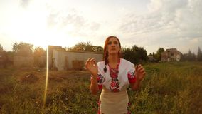 A young woman in a traditional Urainian folk costume throws a water-melon for the camera and catches it back into her hands. Collection, a girl in a traditional stock video footage