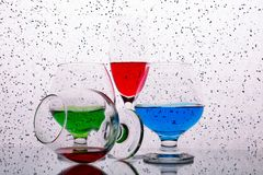 Collection of glasses with colored drinks. Set of glasses with colorful drinks on white with dots background stock images