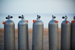 Collection of grey scuba diving air oxygen tanks. Collection of grey scuba diving air oxygen tanks waiting lined up royalty free stock photos