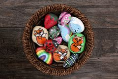 Collection of Hand Painted Colorful Cartoon Rocks in w Wicker Ba stock image