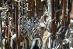 A Collection of Horse Bits Hanging Up Against Out of Focus Background - Selective Focus stock photography