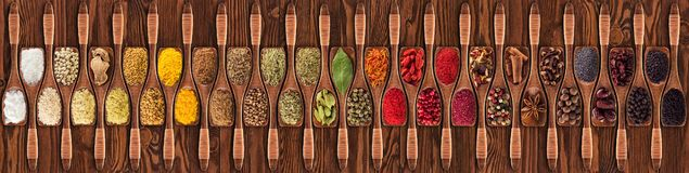 Spices and herbs from different countries in wooden spoons. Colorful seasonings on table background, top view. Collection of Indian condiments and herbs in stock image
