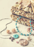A collection of jewelry in jewelry box decorated with seashells. Royalty Free Stock Photos