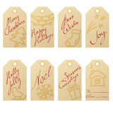 Collection of kraft paper christmas gift tags with hand drawn holiday symbols and handwritten greetings. Collection of textured kraft paper christmas gift tags Stock Images