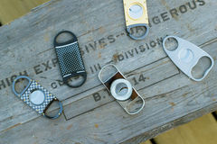 Collection of luxury cigar cutters placed on antique explosive box. High-end cigar cutters and vintage/ antique wooden explosive container. Photo is taken royalty free stock photo