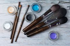 Collection of make up products on wooden background Top view. Collection of make up products: professional brushes and eyeshadows on wooden background. Top view Royalty Free Stock Image