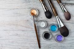 Collection of make up products on wooden background with copyspace. Collection of make up products: professional brushes and eyeshadows on wooden background. Top Royalty Free Stock Images