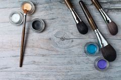 Collection of make up products on wooden background with copyspace. Collection of make up products: professional brushes and eyeshadows on wooden background with Royalty Free Stock Photo
