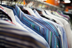 Collection of male shirts on rack. Hangers with colorful male shirts in fashion mall, close up. Shallow depth of field, focus on striped garment Stock Photo