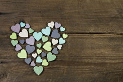 Collection of many handmade hearts in natural colors on old wood. En background.Idea for a valentine greeting card Stock Image
