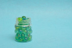 A collection of marbles. In a plastic jar displayed on a blue background Royalty Free Stock Images