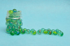 A collection of marbles. In a plastic jar displayed on a blue background Royalty Free Stock Photos