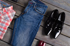Collection of men's clothing. Collection of men's clothing and accessories on a wooden background Stock Image