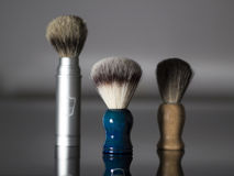 Collection of men's shaving brushes. Collection of men's luxury shaving brushes. The background is black and reflective. Could be used as advertisement for royalty free stock photos