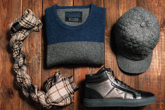 Collection of men's warm autumn clothes for interenet shop. Collection of men's warm autumn clothes on a dark wooden background. scarf, cap, shoes, sweaters Royalty Free Stock Images