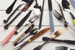 Collection of modern and antique cutlery, top view. Top view on various forks, knives and spoons. Set of assorted cutlery with fancy handles, flat lay on white Stock Photography