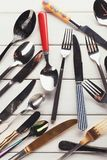 Collection of modern and antique cutlery, top view. Top view on various forks, knives and spoons. Set of assorted cutlery with fancy handles, flat lay on white Stock Image
