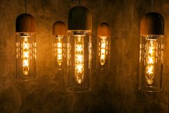 Collection of modern glowing bulbs hanging near wall.  royalty free stock photography