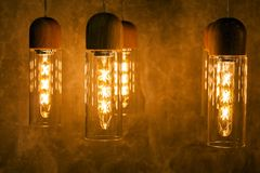 Collection of modern glowing bulbs hanging near wall.  royalty free stock photos