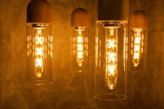 Collection of modern glowing bulbs hanging near wall.  royalty free stock images