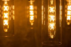 Collection of modern glowing bulbs hanging near wall.  royalty free stock photo