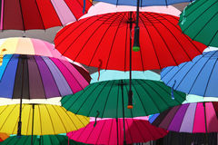 Collection of multi colored umbrellas hanging up. Collection of multi colored umbrellas hanging up in an open position over a street offering shade & protection stock photos
