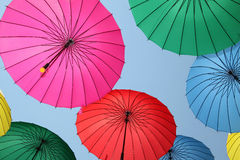 Collection of multi colored umbrellas hanging up. Collection of multi colored umbrellas hanging up in an open position over a street offering shade & protection Royalty Free Stock Images