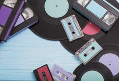 Collection of music tapes, records and video cassettes on wooden. Collection of music tapes, records and video cassettes on old wooden background. Retro concept stock photography